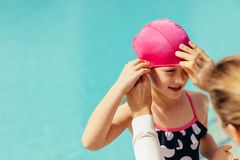 Girl getting ready for swimming lessons. Female coach adjusting swimming cap on girl. Cute girl getting ready for swimming lessons at the pool stock images