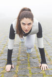 Girl Getting Ready to Run. A close up image of female kneeling, preparing to start Stock Photos