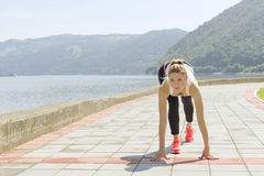 Girl Getting Ready to Run. Image of female preparing to start Royalty Free Stock Photography