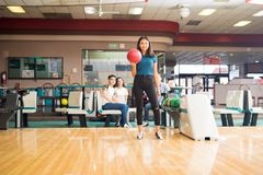 Girl Getting Ready To Throw Bowling Ball In Club. Full length of confident girl getting ready to throw bowling ball in club stock photography