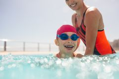 Girl learning to swim in a pool. Girl getting swimming lesson in a outdoor pool with her mother. Girl wearing swim cap and goggles learning to swim with mothers royalty free stock photos