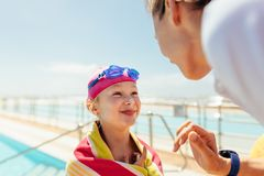 Girl getting swimming lessons. Cute girl after swimming lesson standing by the pool with her coach. Kid drying off after swimming listening to the trainer stock photography