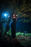 Girl ghost with black eyes standing near a tree at night. Day Halloween Stock Image