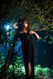 Girl ghost with black eyes standing near a tree at night. Day Halloween royalty free stock photo