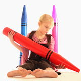 Girl with giant crayons. Girl with giant red, blue and pink color crayons stock photography