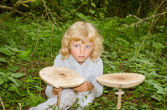 Girl with giant parasol mushroom Stock Image