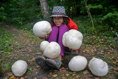 Girl with Giant puffballs Stock Images