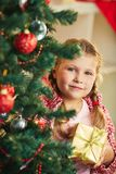 Girl with gift. Adorable girl with giftbox looking at camera out of decorated firtree royalty free stock images