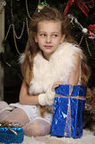 Girl with a gift in blue packaging Stock Photography