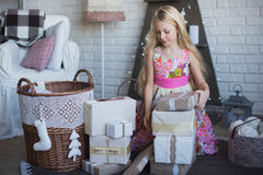 Girl with gift box in hands is happy considers preparation for the holiday, packaging, boxes, Christmas, New Year, lifestyle, holi Stock Images