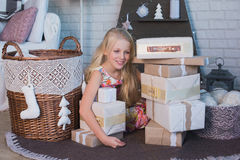 Girl with gift box in hands is happy considers preparation for the holiday, packaging, boxes, Christmas, New Year, lifestyle, holi Stock Image