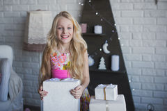 Girl with gift box in hands is happy considers preparation for the holiday, packaging, boxes, Christmas, New Year, lifestyle, holi Stock Photo