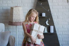 Girl with gift box in hands is happy considers preparation for the holiday, packaging, boxes, Christmas, New Year, lifestyle, holi Royalty Free Stock Photo