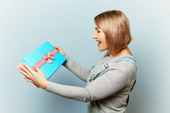 Girl with gift box in her hands on a blue background. Girl with bouquet of flowers in her hands. Flowers, Spring, Romance, March 8 Royalty Free Stock Photography
