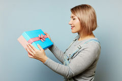 Girl with gift box in her hands on a blue background. Girl with bouquet of flowers in her hands. Flowers, Spring, Romance, March 8 Stock Images