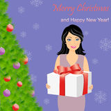 Girl with gift box near Christmas tree Royalty Free Stock Images