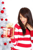 Girl with gift box next to white christmas tree Stock Photography