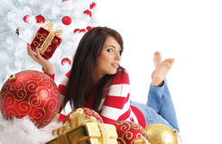 Girl with gift box next to white christmas tree Royalty Free Stock Images