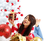Girl with gift box next to white christmas tree Stock Image