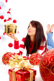Girl with gift box next to white christmas tree Stock Images