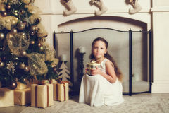 Girl with gift box sitting near christmas tree, vintage toned Royalty Free Stock Image