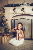 Girl with gift box sitting near christmas tree, vintage toned Stock Image