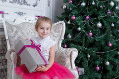 Girl with gift-box under Christmas tree Stock Image