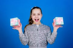 Girl with gift boxes blue background. Black friday. Shopping day. Cute child carry gift boxes. Surprise gift box royalty free stock photography