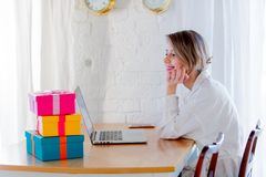 Girl with gift boxes and laptop computer royalty free stock images