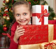 Girl with gift boxes near christmas tree, happy holiday and winter celebration Stock Photo