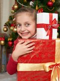 Girl with gift boxes near christmas tree, happy holiday and winter celebration Stock Images