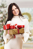 Girl with gift boxes near christmas tree. Stock Image
