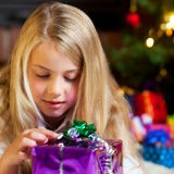 Girl with gift before christmas tree Royalty Free Stock Photo