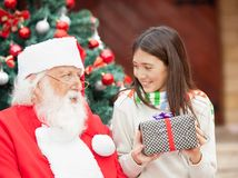 Girl With Gift Looking At Santa Claus Stock Photo