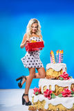 Girl with gift near a cake Stock Photos
