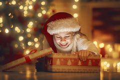 Girl with gift near Christmas tree Stock Images