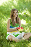 Girl with gift in the park at green grass. Stock Photography
