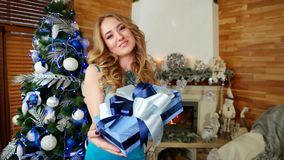 Girl and gift, a portrait of a young woman holding out a Christmas present, a female gives a gift, girl with a gift at stock footage