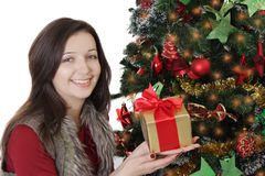 Girl with gift and red ribbon under Christmas tree Stock Image