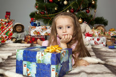 The girl with a gift under the Christmas tree Royalty Free Stock Image