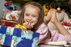 The girl with a gift under the Christmas tree Stock Photos