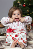 The girl with a gift under the Christmas tree Stock Image