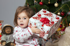 The girl with a gift under the Christmas tree Royalty Free Stock Images