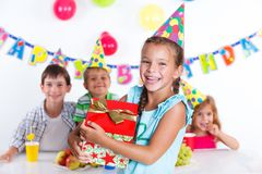 Girl with giftbox at birthday party. Beautiful girl with giftbox looking at camera having fun at birthday party with his friends on background royalty free stock image
