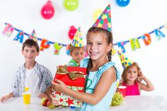 Girl with giftbox at birthday party. Beautiful girl with giftbox looking at camera having fun at birthday party with his friends on background royalty free stock photos