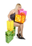 Girl with gifts. The young girl is surrounded by gifts in beautiful boxes Royalty Free Stock Photo
