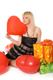 Girl with gifts. The young girl sits among gifts with a balloon in a hand in the form of heart Royalty Free Stock Image