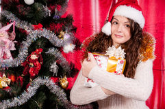 Girl with gifts near a Christmas tree Royalty Free Stock Photos