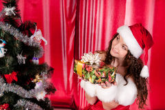 Girl with gifts near a Christmas tree Stock Images