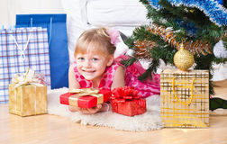 Girl with gifts near a New Year tree Royalty Free Stock Photography